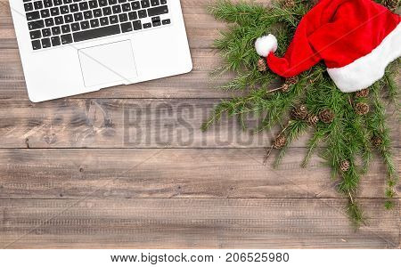 Christmas decoration. Office desk laptop red hat Christmas tree branches. Flat lay on rustic wooden background