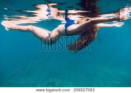 Woman in blue bikini with long hair floating in quiet ocean. Underwater photo