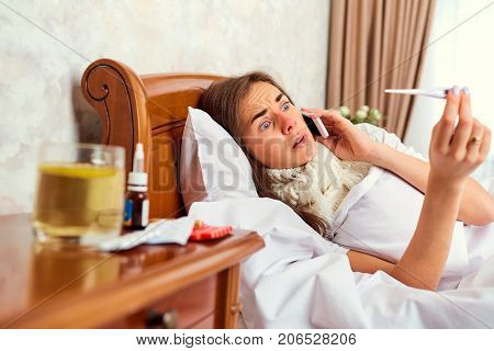 A sick girl with a thermometer on the bed calls the doctor on the phone. Virus. Flu.