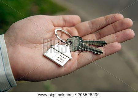the owner of the apartment holds the keys in his hand