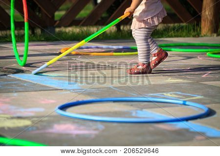 Small girl play hula hoops on playground scratched with chalk.
