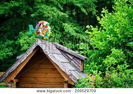 Small colourful vane on wooden hut roof.