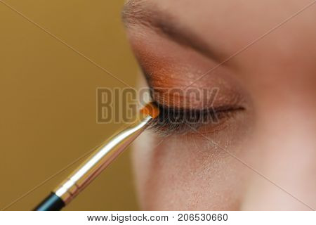Visage concept. Close up woman getting make up on eyelids. Applying eyeshadow with brush closed eyes.