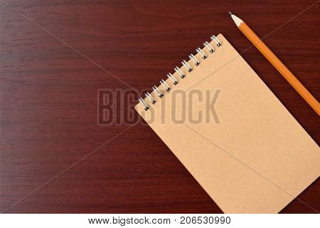 Top view of open spiral blank notebook with pencil on wood paper background. Open vintage notebook. Empty notebook paper for text with  pencil . office concept top view.Copy space. Space for text.