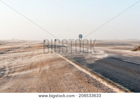 Sand being blown over the B2-Road near Longbeach in the Namib Desert on the Atlantic Coast of Namibia
