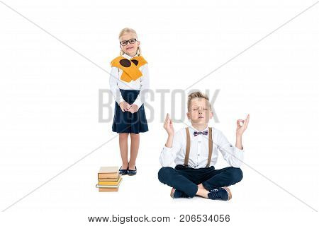 adorable little girl in eyeglasses smiling at camera while boy meditating with books isolated on white