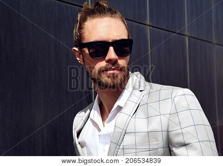 portrait of sexy handsome fashion male model man dressed in elegant white checkered suit posing near dark blue wall in the street background in sunglasses