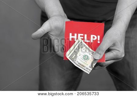 Man in stress holding one dollar bill and Help message selective color studio photo