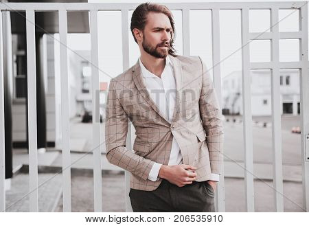 portrait of sexy handsome fashion male model man dressed in elegant beige checkered suit posing on the street background