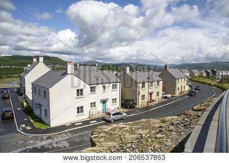 Swansea, UK: May 22, 2016: Overview of a new housing development still under construction. Although owners are occupying their new homes, the road has yet to be finished.