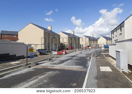 Swansea, UK: May 22, 2016: A new housing development under construction. A safety fence restricts access to the construction zone.