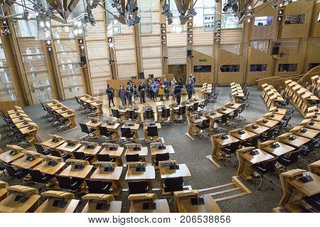 Edinburgh, Scotland, UK: May 27, 2016: An official tour guide explains the design and functions of the Debating Chamber in the Scottish Parliament to a tour group.