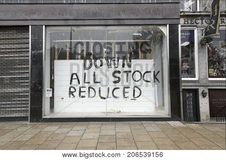Edinburgh, UK: May 29, 2016: A shuttered shop with a 'closing down' sign written on the window. Many traders are going out of business because of the turn down in the economy.