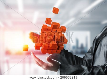 Cropped image of business woman hands holding multiple orange cubes in hands with sunlight on office background. Mixed media.