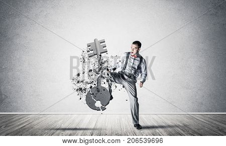 Determined businessman in empty interior breaking with leg kick stone key figure