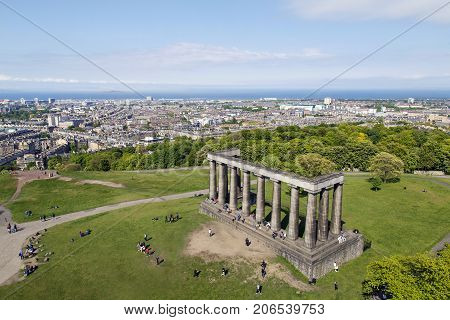 Edinburgh, UK: May 28, 2016: High angle view of the Carlton Hill National Monument in Edinburgh. A memorial to the soldiers and sailors of the Napoleonic Wars with the Edinburgh cityscape behind.
