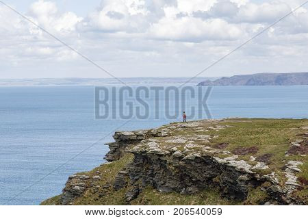 Cornwall, UK: April 14, 2016: A tourists enjoys a cliff top walk at Tintagel. Tintagel is a popular holiday destination because of its dramatic cliff tops and coastal scenery.