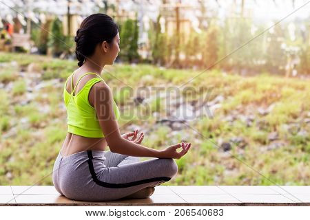 young woman in sportswear meditating while sitting in lotus pose