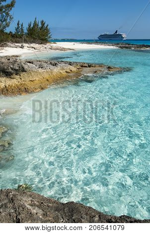 The view of crystal clear waters of Half Moon Cay with a cruise ship in a background (Bahamas).