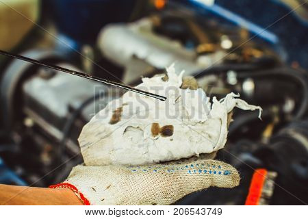 man checking oil level in car engine