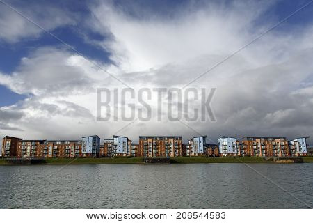 Quayside Apartment Building on reclaimed land with a dramatic cloudscape.