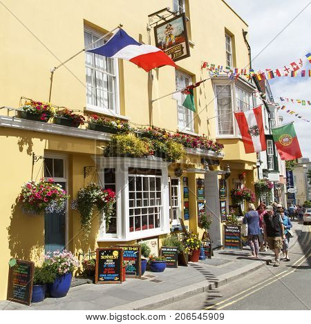 Tenby, UK: July 05, 2016: Tourists walk past the brightly painted Buccaneer Inn in Tenby. A very popular pub with visitors during the summer time with its flags and hanging baskets.