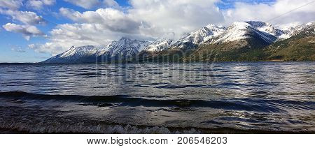 Grand Tetons shrouded in clouds reflection off Jackson Lake