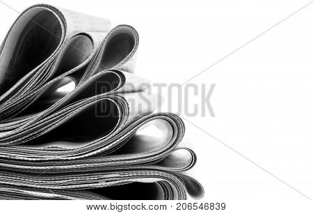 Newspapers folded and stacked on white background
