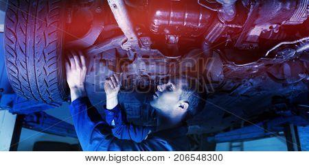 Male mechanic under car in garage