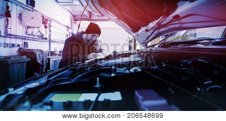 Mechanic watching the car engine in garage