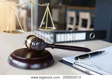 Close up of gavel and scales of justice and Report the case with paper on wooden table in office Law and justice concept.