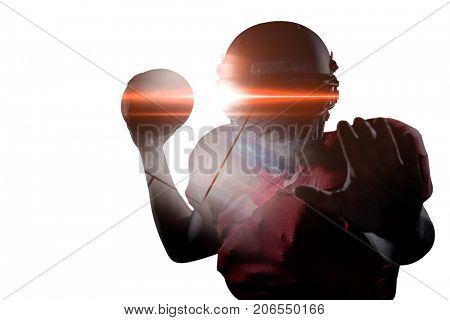 Portrait of sportsman defending while holding American football against black background
