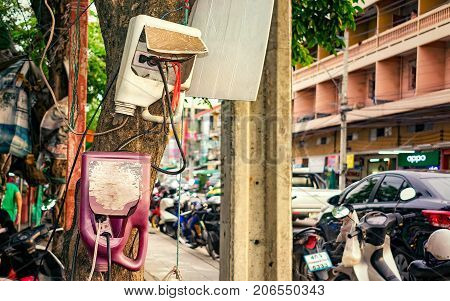 BANGKOK THAILAND - SEPTEMBER 14: Locals use modified plastic jugs to weather proof electrical connections on extension cords on a tree outdoor on September 14 2017 in Bangkok.