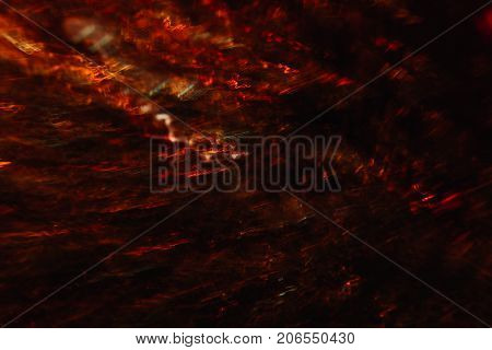 Abstract background of colorful crankles in motion on black. Bokeh of defocused curves, blurred neon yellow and red leds, hellfire and smoke, abyss and seven circles of hell
