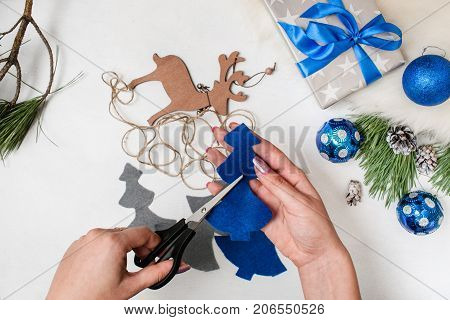 Holiday preparation. Christmas and New Year. Unrecognizable woman scissors out felt fir tree. Ornament balls, gift box and wooden deer on desk, top view. Home and restaurant decoration concept