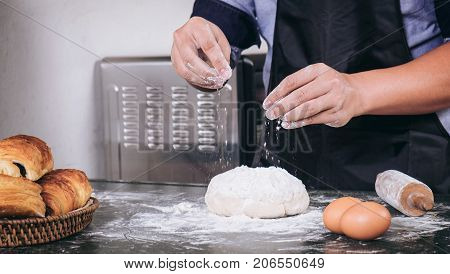 Close up of Man hands sprinkling flour over fresh dough with ingredients on black background.