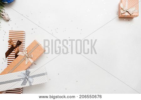 Festive background of Christmas presents. Gift boxes on white background with silver star tinsels top view. Holidays, New Year, festival and Christmassy concept