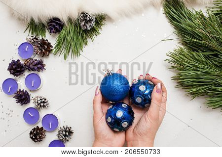 Festive background of Christmas decoration. Small tea candles with pine branch and ornament balls in hand, top view and copy space. Holiday, home decor and celebration concept