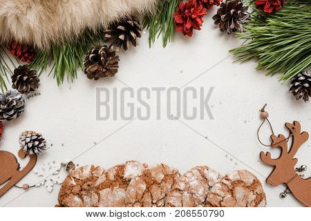 Festive background of Christmas and New Year. Decoration from pine branch with strobila, wooden ornaments and sweet cakes on white backdrop, top view copy space. Holidays and homemade decor concept
