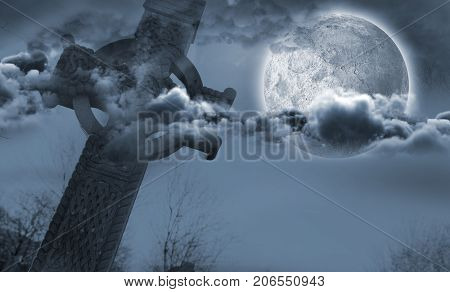 Celtic cross in front of moon behind clouds