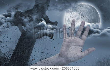 Hand by side of celtic cross in front of moon