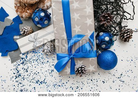 Background of Christmas decor and gifts. Wrapped and taped presents, ornament blue balls, sweet cakes and felt fir tree with spangles spread around. Festive backdrop of handmade decoration concept