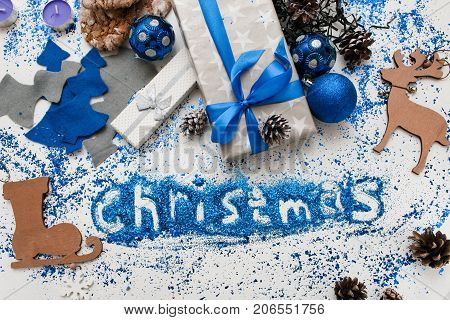 Christmas inscription. Decor and gifts backdrop. Top view wrapped presents and different handmade ornaments, bright spangles spread around. Festive background of holiday decoration concept