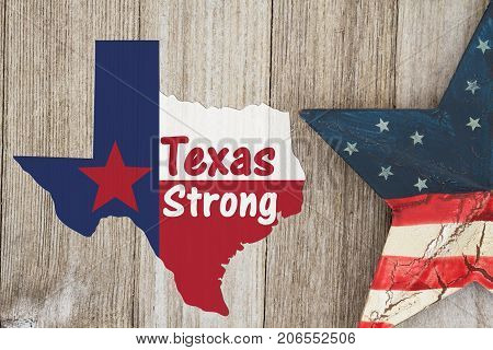 A rustic old Texas Strong message Texas flag in shape of map with American star on weathered wood background with text Text Strong