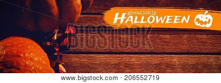 Graphic image of ghoulishly Halloween text against pumpkins and petals on wooden table
