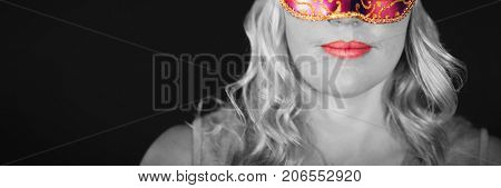 Portrait of young woman in masquerade mask against black background