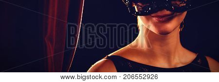 Portrait of woman in masquerade mask by curtain at stage
