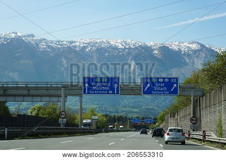 Salzburg Austria - April 22 2016 : On Autobahn (German Highway) Road sign indicating direction to Innsbruck and Munich. With beautiful mountain view in background.