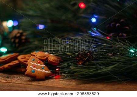 Festive background of Christmas decoration. Pine branch with fairy lights and homemade cookies on wooden table, close up. Family celebration, New Year traditions and handmade decor concept