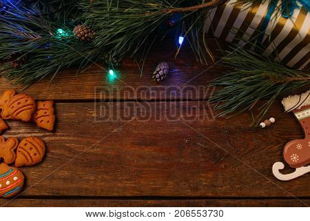 Christmassy decoration background. Pine branch with fairy lights, present box and homemade cookies on wooden background, top view copy space. Family celebration and New Year traditions concept
